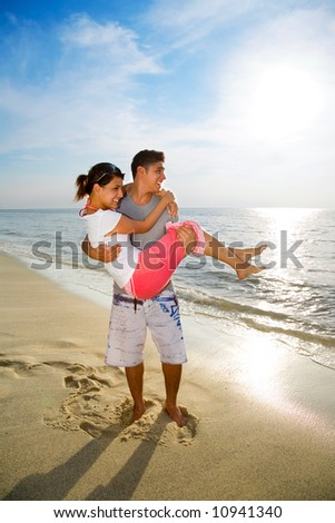 loving happy couple with the man carrying the woman on the beach