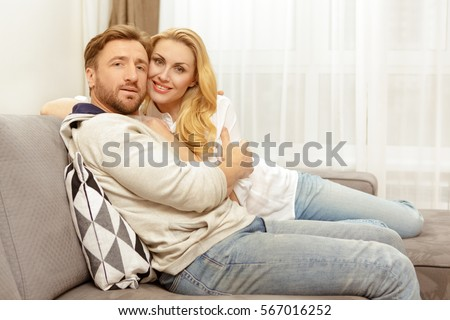 Loving husband and wife. Beautiful happy mature couple embracing relaxing together at home sitting on the sofa smiling to the camera happiness love romance romantic relationship family move concept