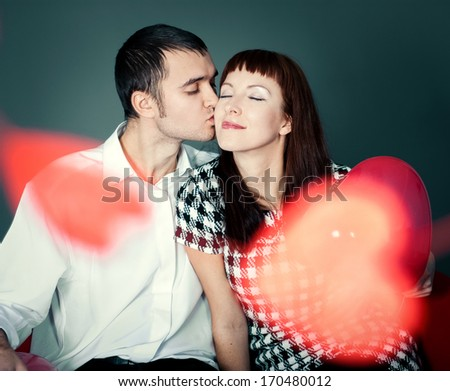 Loving kissing couple with balloon hearts - stock photo
