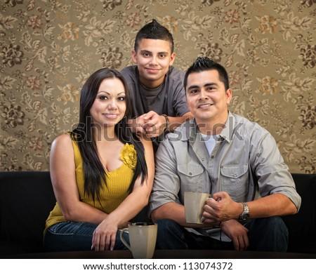 Loving Latino family of three sitting together - stock photo