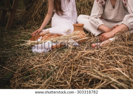 loving man and woman in a linen dress on a background of haystacks with  homemade bread
