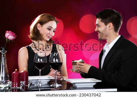 Loving man giving present to woman while having wine at restaurant table - stock photo