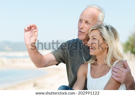 Loving mature couple enjoying a day at the sea standing in a close embrace overlooking the ocean having an animated discussion and gesturing - stock photo