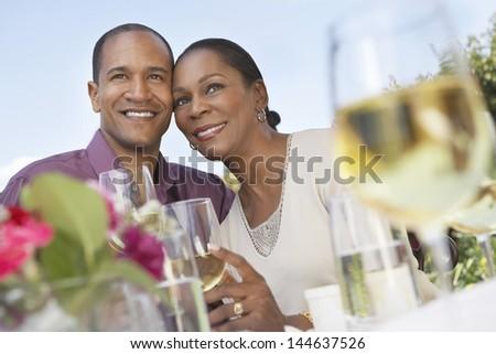 Loving middle aged couple celebrating with white wine outdoors - stock photo