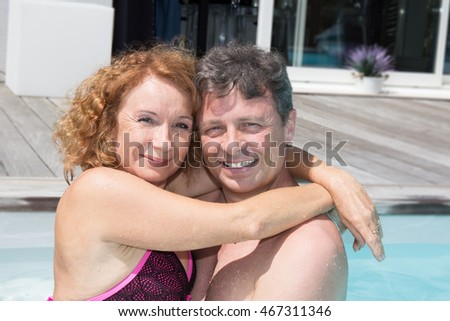 Loving middle aged couple spending romantic time by pool