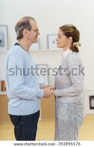 Loving middle-aged couple standing facing each other holding hands and smiling into each others eyes, side view - stock photo