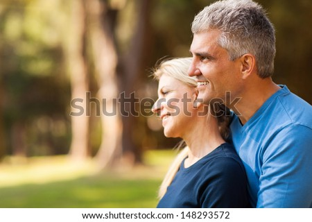 loving middle aged husband with wife outdoors looking forward - stock photo