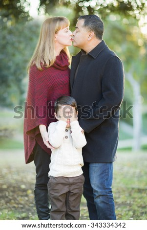 Loving Mix Race Couple Kissing As Young Son Hides His Eyes. - stock photo