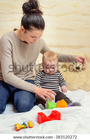 Loving Mom Giving Colored Plastic Toys to her Crying Baby and Play Together at Home. - stock photo