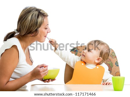 loving mom spoon feeding her playful child girl isolated on white - stock photo