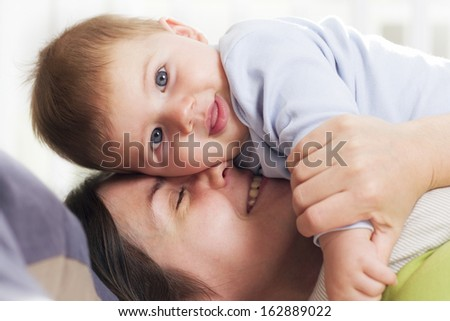 Loving moments: Happy mother and baby boy with beautiful blue eyes hugging when lying down in bed.