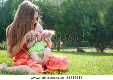 loving mother and baby on natural background - stock photo
