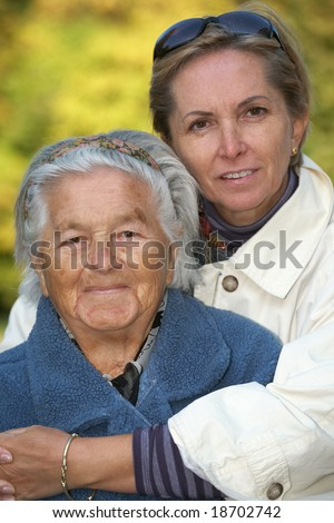 Loving mother and daughter in the park. Focus on the elderly woman; - stock photo