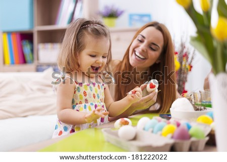 Loving mother and her baby painting easter eggs  - stock photo