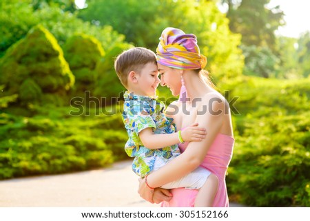Loving Mother and son playing in summer park - stock photo