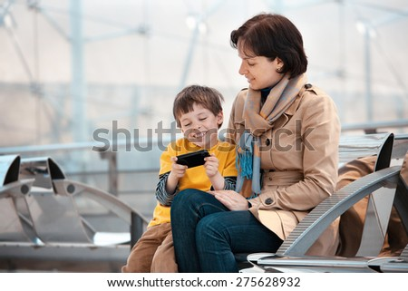Loving mother and son using smartphone at airport, going on holiday - stock photo