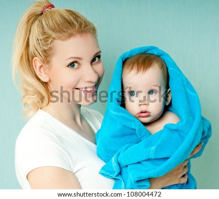 loving mother holding a baby in a towel - stock photo