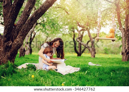 Loving mother in long white dress reading book to toddler son on cozy picnic in spring garden, soft warm toned - stock photo