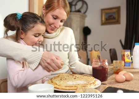 loving mother making crepes with little girl - stock photo