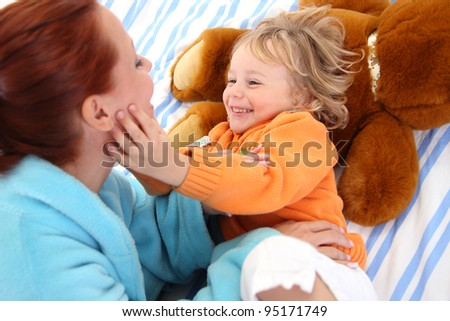 Loving mother playing with her baby boy - stock photo
