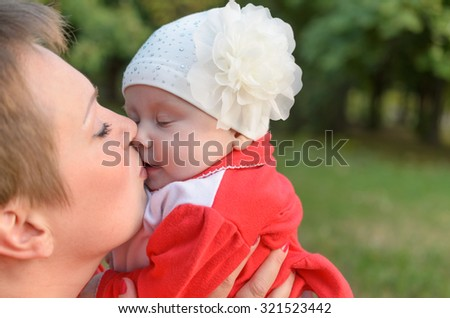 Loving mother tenderly kissing her child with affection. - stock photo