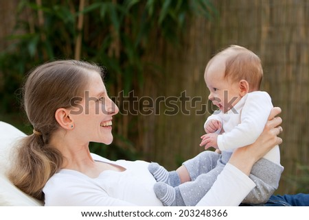 Loving mother with her newborn baby holding it up in front of her with a joyful smile reciprocated by a happy laughing infant, profile view