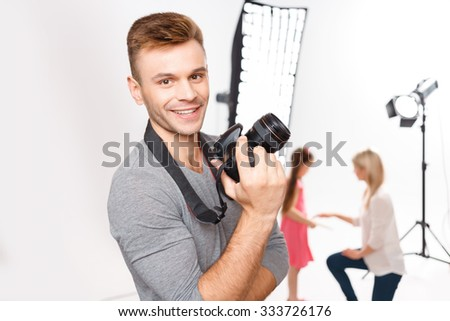Loving my job. Appealing young male photographer with his camera grins charmingly while model and makeup artist are both busy preparing. - stock photo