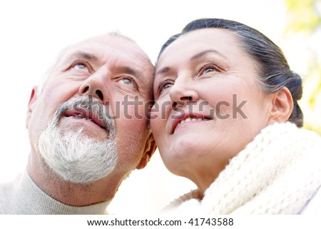 Loving older couple looking up with a smile