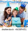 Loving parents celebrating their son's birthday in the kitchen - stock photo