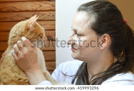 Loving pet - tender moment between woman and her ginger cat