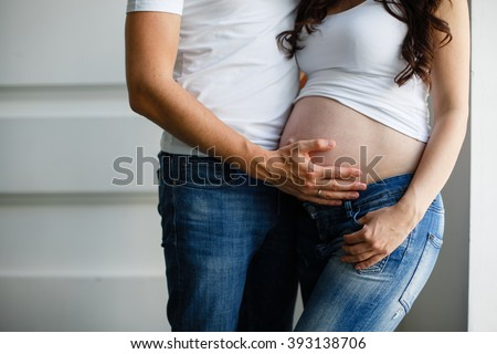 Loving pregnant couple holding the belly  - stock photo