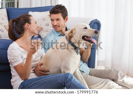 Loving relaxed young couple with wine glass and pet dog sitting in living room at home - stock photo