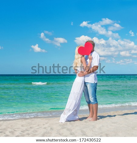 Loving romantic hug couple at sunny sea beach with red heart symbol - St.Valentines Day concept - stock photo