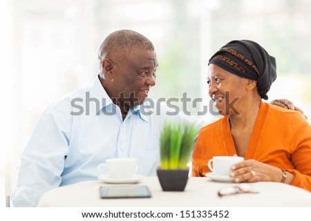 loving senior african couple relaxing at home - stock photo