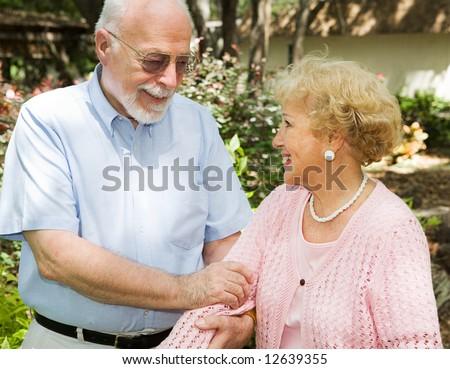 Loving senior couple enjoying a stroll outdoors. - stock photo