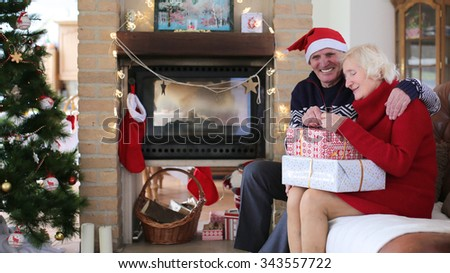 Loving senior couple exchanging gifts on christmas morning or new year day in decorated living room with fireplace and xmas tree. - stock photo