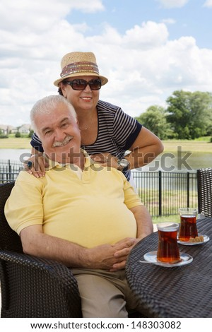 Loving senior couple having drinks on an outdoor patio giving the camera beautiful beaming smiles with the woman posing behind her husband with her hands on his shoulders - stock photo