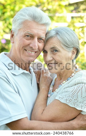 Loving senior couple on a background of trees in summer - stock photo