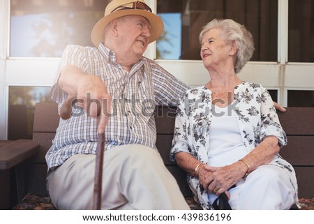 Loving senior couple relaxing on a bench outside their home. Happy retired couple having a break. - stock photo