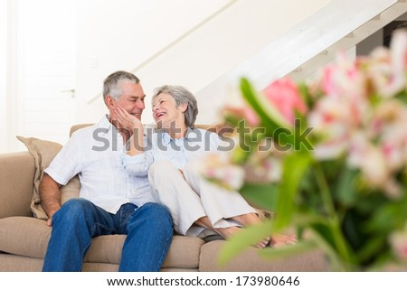 Loving senior couple relaxing on sofa at home - stock photo