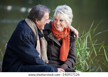 Loving senior couple sitting and talking at the park - stock photo