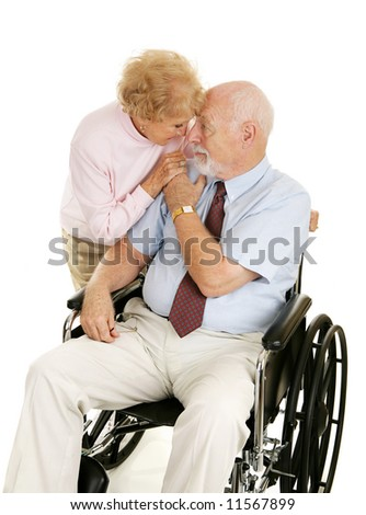 Loving senior couple.  Wife is caring for her husband who is confined to a wheelchair.  Isolated on white. - stock photo