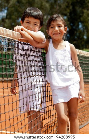 Loving sibblings at a tennis court next to the net - stock photo