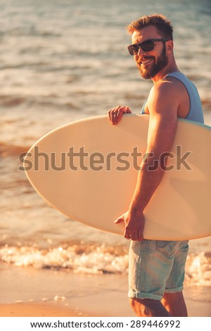 Loving summer. Side view of young man holding skimboard and smiling at camera while walking along the beach - stock photo