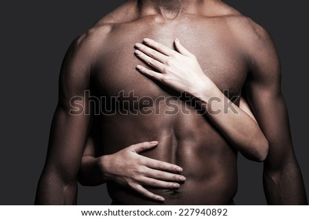 Loving this body. Close-up of shirtless African man with female hands embracing his torso against grey background  - stock photo