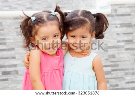 Loving twin sisters two years outdoors playing - stock photo