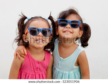 Loving twin sisters two years with sunglasses outdoors playing - stock photo