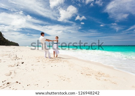 Loving wedding couple dancing on beach in white dresses - stock photo