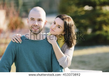 Loving young calm and smiling couple boyfriend and girlfriend or husband with wife sitting on the bench hug copy space - stock photo