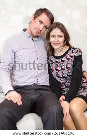 Loving young Caucasian couple sitting on sofa together - stock photo